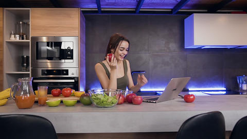 Beautiful high-spirited positive young woman eating fresh apple and using laptop Live Action