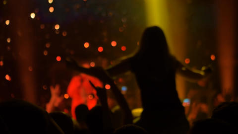 Super slow motion: people silhouettes partying at rock concert in front of stage Live Action
