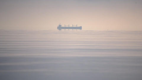 Silhouette of cargo ship boat on horizon of sea, of ocean in morning Live Action