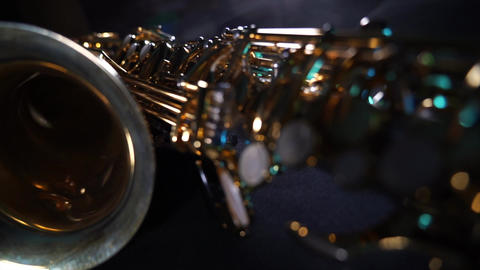 Golden shiny alto saxophone on black background with blue smoke Live Action