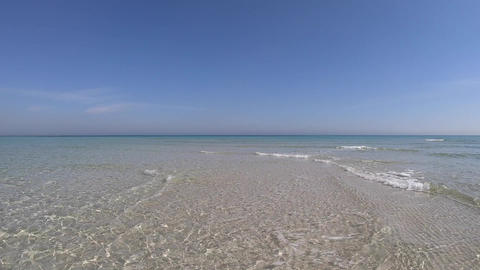 Slow-motion of Crystal clear shallow water and white sand with blue sky Live Action