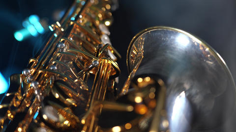 Golden shiny alto saxophone with blue smoke. Concept of grace and elegance Live Action