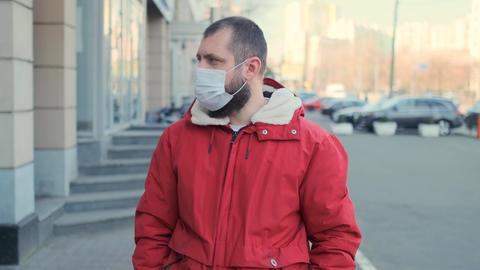 Young hipster bearded man wearing protective mask on street background. Health Live Action