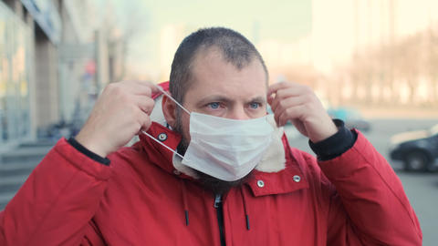 Shocked bearded hipster man putting on a protective mask. The guy in fear puts Live Action