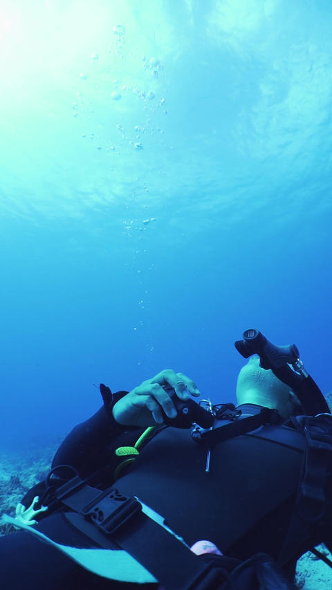 Vertical video of scuba diving. A diver is making a bubble ring Live Action