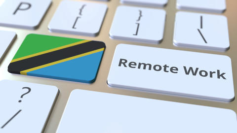 Remote Work text and flag of Tanzania on the computer keyboard. Telecommuting or Live Action