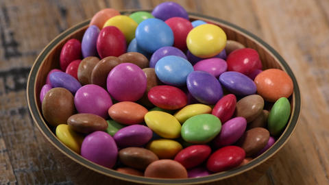 Colorful candies in a wooden bowl case isolated on wood background Live Action