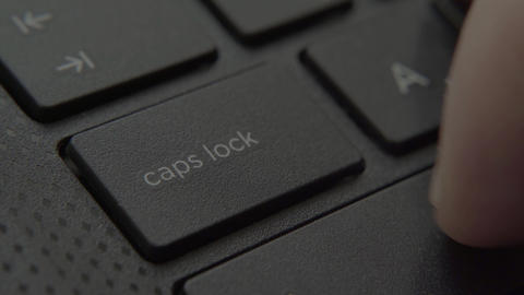 The finger presses the capslok button on the keyboard Live-Action