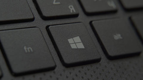 The finger presses the Windows button on the keyboard Live-Action