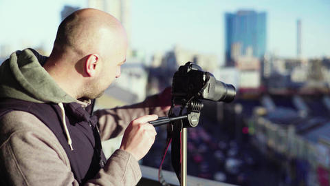 Cameraman photographer with a camera DSLR on a tripod in the city shoots video Live-Action