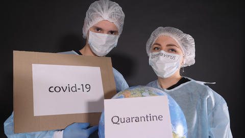 Man and a woman in protective clothing hold signs with the words covid-19 and Live-Action