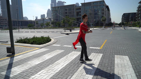 Young girl jumping with jump rope on the green grass with cityscape of Dubai 실사 촬영