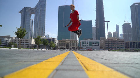 Young girl jumping with jump rope on the green grass with cityscape of Dubai Live Action