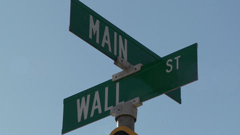 A street sign indicates the intersection of Main and Wall Streets Live Action