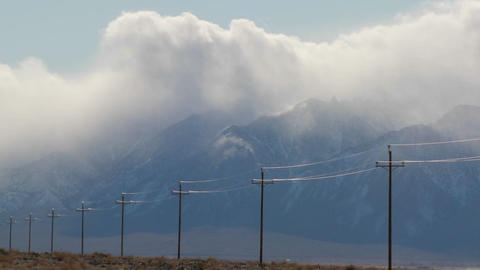 Time lapse over the Sierra Nevadas with telephone poles in the foreground Footage