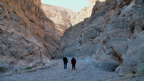 A senior man and woman hike in a canyon in Death Valley Footage