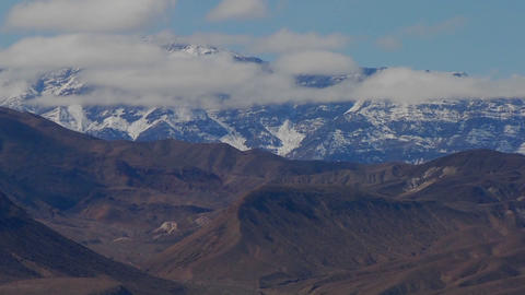 A slow move back on a time lapse of a beautiful mountain range in winter in Death Valley Footage