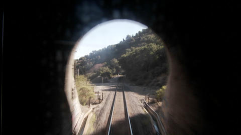 An exciting point of view shot from the front of a train coming out of a long tunnel at high speed Footage