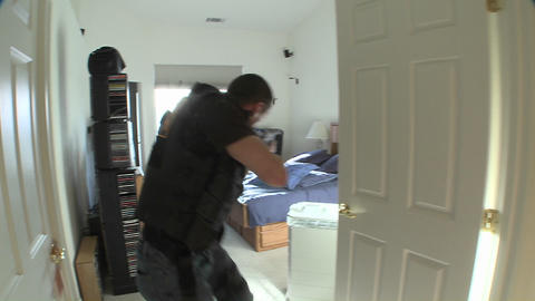 A SWAT team with DEA officers clears a house during a drug raid Footage