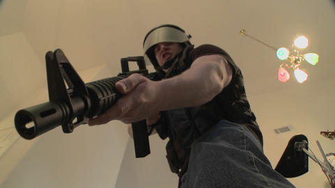 A SWAT Team With DEA Officers Clears A House During A Drug Raid And Holds A Suspect At Gunpoint stock footage
