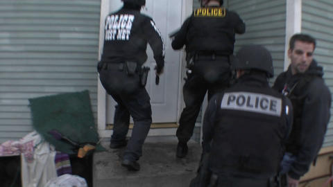 A SWAT team of DEA agents conduct a raid on a crack house Stock Video Footage