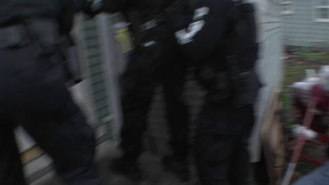 A SWAT team of DEA agents conduct a raid on a crack house Footage