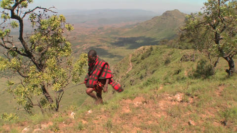 A Masai warrior walks along the edge of the world in... Stock Video Footage