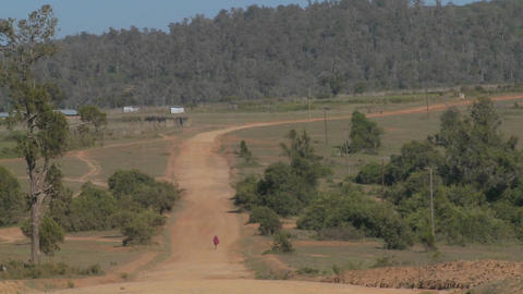 A man walks in the distance on a lonely dusty dirt road... Stock Video Footage