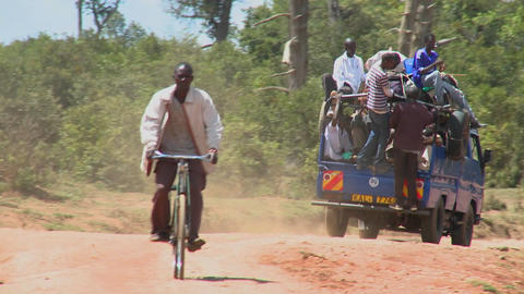 A van crowded with passengers makes its way along a dirt road in East Africa Footage