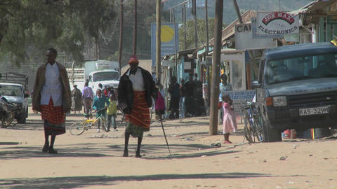 Pedestrians walk on the dirt streets of Maralal in... Stock Video Footage