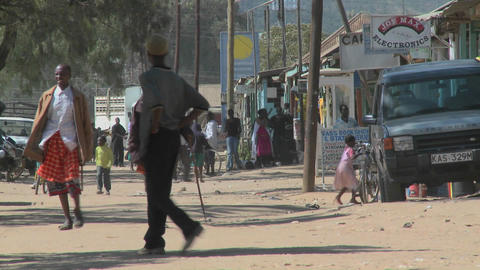Pedestrians walk on the dirt streets of Maralal in Northern Kenya Footage