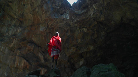Majestic shot of a Masai warrior standing in a cave in Kenya Stock Video Footage