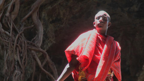 A young Masai man standing in a pool of light in a cave in Kenya Footage