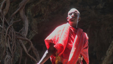 A young Masai man standing in a pool of light in a cave... Stock Video Footage