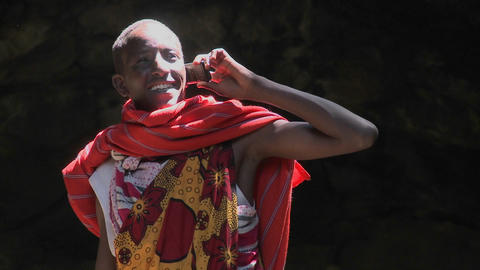 Tilt up to a Masai man speaking on a cell phone Stock Video Footage