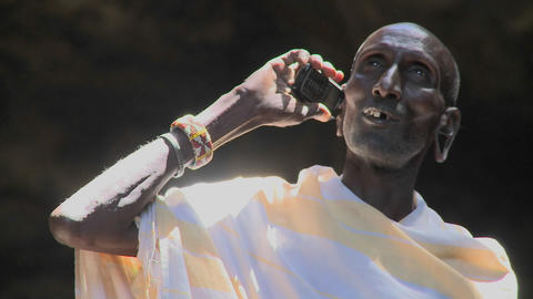 An old Masai man speaks to friends on a cell phone Footage