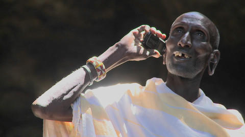 An old Masai man speaks to friends on a cell phone Stock Video Footage