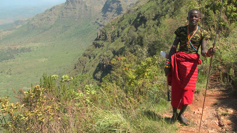 Tilt up to reveal a Masai warrior standing at the edge of... Stock Video Footage