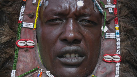 A good closeup of a Masai tribal warriors face with beads and headdress Footage