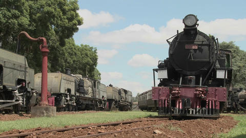 Old rusting steam trains sit in a railway yard Stock Video Footage