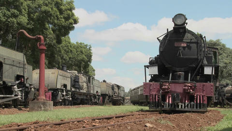 Old rusting steam trains sit in a railway yard Footage