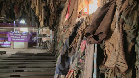 Tilt up reveals a Rwandan church following the genocide there with clothes of victims hung on walls Live Action