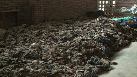 A Cross Sits Amongst The Scattered Clothing Of Victims Following A Genocide In A Church In Rwanda stock footage