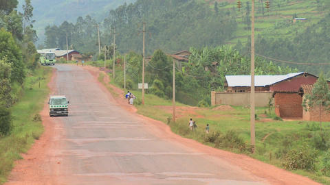 A minibus travels down a rural road in Rwanda Stock Video Footage