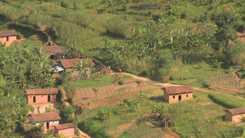 Zoom out from villagers and farmers to reveal the steep and luxurious terrace farms of Rwanda Footage