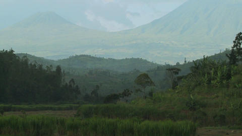 Slow zoom out reveals the Virunga volcano chain on the Rwanda Congo border Footage