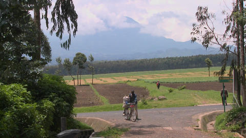 A man walks his bicycle down a rural road in Rwanda with the Virunga volcanos in the background Footage