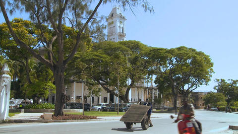 A man pushes a hand cart along a road in Stone Town,... Stock Video Footage