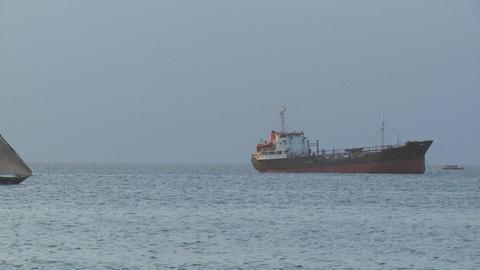 A dhow sailboat sails past a modern cargo ship off the... Stock Video Footage