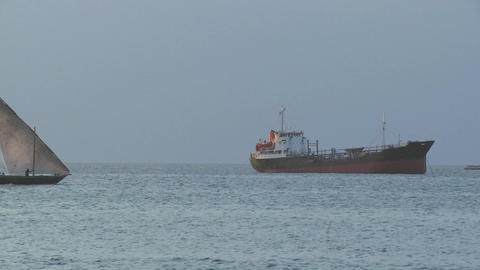 A dhow sailboat sails past a modern cargo ship off the coast of Zanzibar Footage